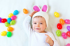Baby boy in bunny hat lying on green blanket with Royalty Free Stock Photos