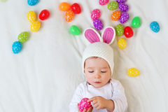 Baby boy in bunny hat lying on green blanket with Stock Photography