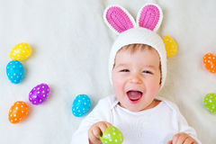 Baby boy in bunny hat lying on green blanket with Royalty Free Stock Photography