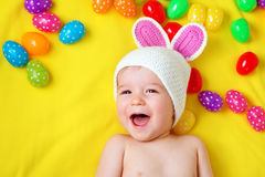 Baby boy in bunny hat lying on yellow blanket with easter eggs. Baby boy in bunny hat lying on yellow blanket with multicolored easter eggs Royalty Free Stock Images