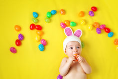 Baby boy in bunny hat lying on yellow blanket with easter eggs Royalty Free Stock Photography