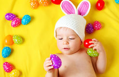 Baby boy in bunny hat lying on yellow blanket with easter eggs Royalty Free Stock Photos