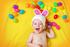 Baby boy in bunny hat lying on yellow blanket with easter eggs Stock Images