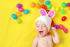 Baby boy in bunny hat lying on yellow blanket with easter eggs Stock Photo