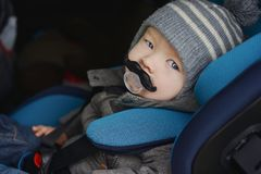 Baby boy in car seat. With funny dummy in mouth Royalty Free Stock Photo