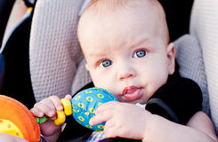 Baby boy in car seat. Holding a toy in his hand Stock Images