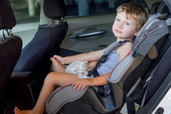 Baby boy in car seat. Portrait of cute toddler boy sitting in car seat. Child transportation safety Royalty Free Stock Photo