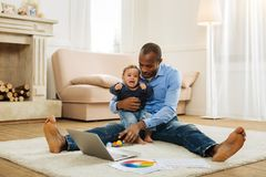 Happy father amusing his crying son. Baby boy. Caring young afro-american father holding a crying curly-haired baby and amusing him while sitting on the floor stock images