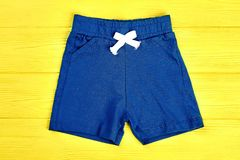 Baby boy casual shorts. Toddler boy brand textile short pants on yellow wooden background. Dark blue kids shorts Royalty Free Stock Image