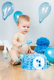 Baby boy celebrating her first birthday with gourmet cake and ba Royalty Free Stock Images