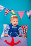 Baby boy in a celebratory cap with a blue background Stock Photography