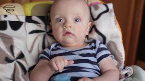 Baby boy in chair. Baby boy reclined in a child seat. boy with blue eyes. the child is in a good mood stock video