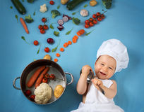 Baby boy in chef hat with cooking pan and vegetables. Baby boy in chef hat with cooking pan and raw vegetables Royalty Free Stock Photo
