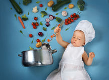 Baby boy in chef hat with cooking pan and vegetables. Baby boy in chef hat with cooking pan and raw vegetables Royalty Free Stock Images