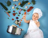 Baby boy in chef hat with cooking pan and vegetables Royalty Free Stock Images