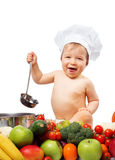 Baby boy in chef hat with cooking pan and vegetables. Baby boy in chef hat with cooking pan and raw vegetables Stock Photo