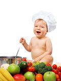 Baby boy in chef hat with cooking pan and vegetables. Baby boy in chef hat with cooking pan and raw vegetables Royalty Free Stock Image