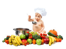 Baby boy in chef hat with cooking pan and vegetables. Baby boy in chef hat with cooking pan and raw vegetables Royalty Free Stock Photos