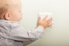 Baby boy child kid turning on the light. Stock Photo