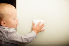 Baby boy child kid turning on the light. Stock Image