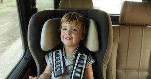 Baby boy in the children`s car seat in the car. Kid smiles stock video footage