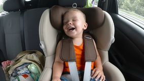 Baby boy in the children`s car seat in the car. Kid smiles, laughs and waves his hands happily. stock footage