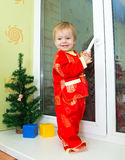 Baby boy in Chinese new year costume stands on the window sill. Near Christmas tree Royalty Free Stock Photography