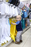Baby boy chooses clothes Stock Photo