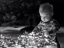 Baby boy with Christmas lights Stock Photo