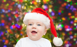 Baby boy in christmas santa hat over blue lights Royalty Free Stock Photography