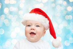 Baby boy in christmas santa hat over blue lights Royalty Free Stock Image