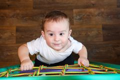 Baby Boy climbs on the net. Adorable baby boy climbs on the net Royalty Free Stock Image