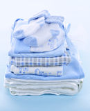 Baby boy clothes. Stack of boy infant clothing for baby shower on blue background Stock Photography