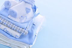 Baby boy clothes. Stack of boy infant clothing for baby shower on blue background Stock Photo