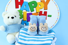 Baby boy clothes with congratulation. On the blue background Royalty Free Stock Photo