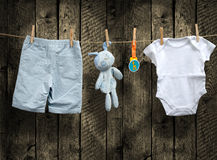 Baby boy clothes and stuffed bunny on a clothesline.  Stock Images