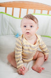 Baby boy in cradle. Baby boy in striprd clothes sitting in cradle Royalty Free Stock Photos