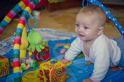 Baby boy crawling on colorful playmat Royalty Free Stock Image