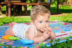 Baby boy crawling with finger in mouth Royalty Free Stock Photo