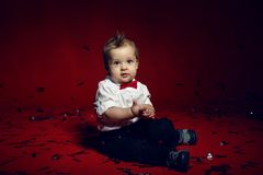 Baby boy crawling on the floor with confetti in Studio Stock Images