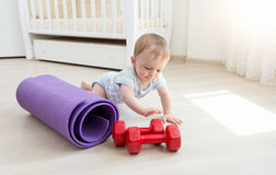 Baby boy crawling on floor and playing with dumbbells Royalty Free Stock Photography