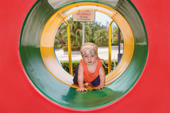 Baby boy crawling with fun through colorful playground tube Stock Photography
