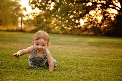 Baby boy crawling in golden sunlight. Baby boy in overalls crawling with sunlit backlighting through trees in the late afternoon stock images