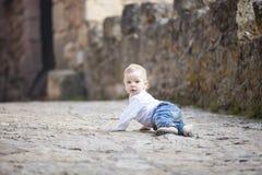 Baby boy crawling on stone paved sidewalk Royalty Free Stock Photos