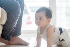 Baby boy crawling towards father. Stock Photos