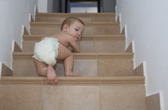 Baby boy crawling up the stairs Stock Photo