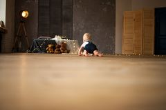 Baby boy crawls against background of toys and garland of glowing light bulbs. Baby boy crawls at the floor against background of toys and garland of glowing stock photography
