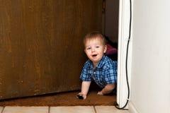 Baby Boy Crawls Through Doorway with a Smile Stock Photos