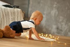 Baby boy crawls and plays with garland of glowing light bulbs. Baby boy crawls at the floor and plays with garland of glowing light bulbs next to the toys stock images