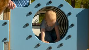 Baby boy crawls in the tube. In the park on the playground stock video
